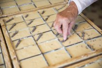 Female hand applying dried lavender to soap bars in handmade soap workshop — Stock Photo