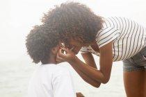 Ritratto di giovane donna che tocca le guance dei figli sulla spiaggia di Ipanema, Rio De Janeiro, Brasile — Foto stock