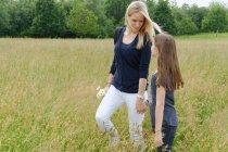 Mãe e filha passeando pelo campo gramado — Fotografia de Stock