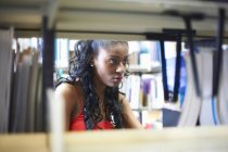 Young female college student searching library shelves — Stock Photo