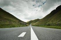 Straße durch grüne Hügel unter bewölktem Himmel Strecken — Stockfoto