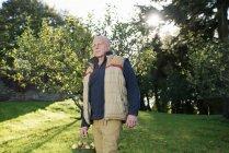 Homem sênior carregando balde de maçãs — Fotografia de Stock