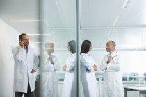 Médicos masculinos y femeninos charlando y hablando por teléfono en la oficina - foto de stock