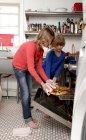 Duas meninas na cozinha, tomando pizza do forno — Fotografia de Stock