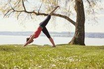 Seitenansicht der Frau, die sich nach vorne beugt, Bein in Yogaposition erhoben — Stockfoto