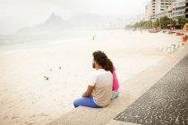 Пара сидящих с видом на пляж Ипанема, Рио-де-Жанейро, Бразилия — стоковое фото
