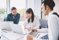 Молодая бизнес-леди и мужчины встречаются за столом заседаний — стоковое фото