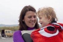 Ritratto di madre che tiene il figlio avvolto in un asciugamano — Foto stock