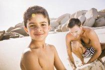 Портрет мальчика и отца, делающих песчаный замок на пляже, Кейптаун, Южная Африка — стоковое фото