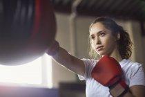Молодая боксерша бьет кулаками в спортзале — стоковое фото