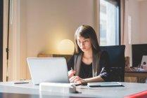 Junge Unternehmerin an Schreibtisch Tippen auf laptop — Stockfoto
