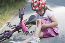 Petite fille avec jambe blessée assise sur la route avec vélo — Photo de stock