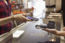Cropped view of womans hands using smartphone to make contactless payment on smartphone — Stock Photo