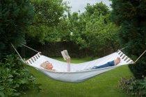 Mujer relajante en hamaca en el jardín - foto de stock