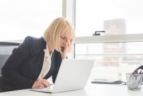 Stressed mature businesswoman working on laptop at office desk — Stock Photo