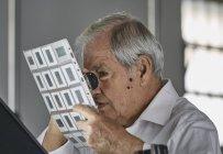 Старший мужчина смотрит на лист слайдов с увеличителем — стоковое фото