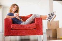 Woman having coffee in armchair — Stock Photo