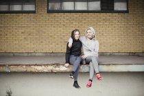 Retrato de duas amigas corredoras sentadas na plataforma do armazém — Fotografia de Stock