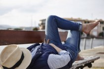 Mature woman lying on bench, hat covering face — Stock Photo