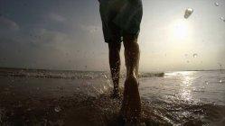 Legs of woman on coastline walking in ocean — Stock Photo