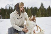 Junger Mann mit Trappermütze streichelt Husky im Schnee, Elmau, Bayern, Deutschland — Stockfoto