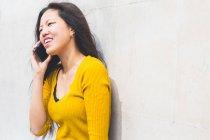 Jovem encostada à parede fazendo chamada telefônica — Fotografia de Stock