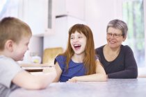 Grandmother and grandchildren laughing at kitchen table — Stock Photo