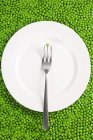 Fork and plate on pea — Stock Photo
