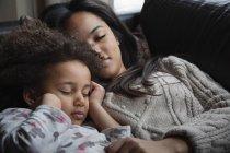 Две сестры спят дома на диване — стоковое фото