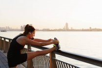 Young female jogger on riverside stretching leg — Stock Photo