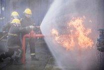 Tres bomberos apagan fuego en instalación de entrenamiento de simulación de incendios - foto de stock