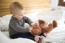Petite fille assise sur le lit, jouant avec les ours en peluche — Photo de stock