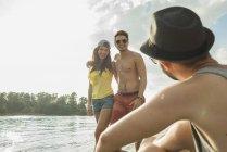 Молодая пара, стоя у озера и говорить с друг — стоковое фото