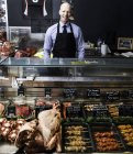 Portrait of butcher, standing behind counter — Stock Photo