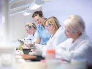 Dentiste professionnel enseignant des apprentis en laboratoire dentaire — Photo de stock