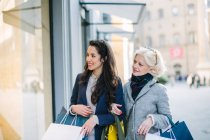 Mother and daughter carrying shopping bags arm in arm window shopping — Stock Photo