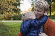Отец и сын обнимаются в парке — стоковое фото