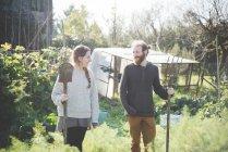 Jeune couple en tenue jardin fourche et pelle — Photo de stock