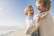 Father on beach carrying son, mouth open smiling — Stock Photo