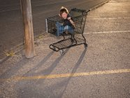 Boy using shopping cart as a vehicle — Stock Photo