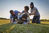 Familia disfrutando de la actividad al aire libre en el parque al atardecer - foto de stock