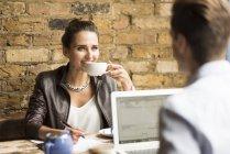 Joven hombre de negocios y mujer tomando té en la cafetería - foto de stock