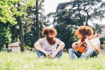 Молоді чоловіки hipster близнюки з червоним борідками, сидячи в park грати на гітарі — стокове фото