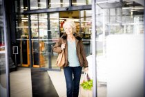 Mature woman exiting supermarket with bag of shopping — Stock Photo