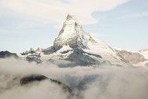 Pico de la montaña nevadas y cielo nublado - foto de stock