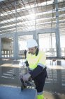Constructeur utilisant une scie rotative sur le chantier de construction — Photo de stock