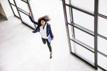 Vue en angle élevé de la femme d'affaires passant par l'entrée du bureau — Photo de stock