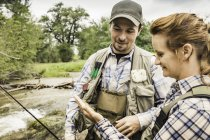 Couple by river preparing for fishing smiling — Stock Photo