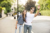Young couple hailing a cab on city street, London, UK — Stock Photo