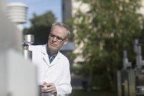Maschio meteorologo monitoraggio apparecchiature meteorologiche presso stazione meteo sul tetto — Foto stock